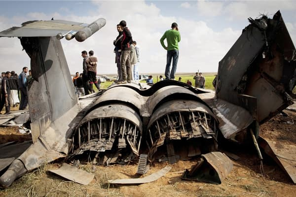Libyans inspect the wreckage of a US F15 fighter jet after it crashed in an open field in the village of Bu Mariem, east of Benghazi, Libya.