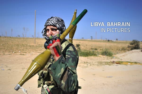 A Libyan rebel fighter flashs the victory sign as he carries rocket propelled grenades at a check point near the key city of Ajdabiya on March 23, 2011 as government forces have encircled the town.