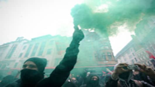 A protester holds up a smoke bomb during a mass demonstration against government financial cuts in central London, on March 26, 2011.
