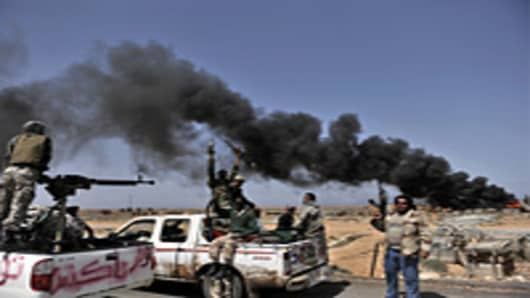 Libyan rebels progress westward from the town of Bin Jawad towards Muammar Gaddafi's home town of Sirte on March 28, 2011 as NATO finally agreed to take over full command of military operations to enforce a no-fly zone in Libya from a US-led coalition.