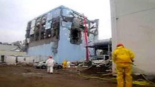 TEPCO workers in protective suits conduct a cooling operation by spraying water at the damaged No. 4 unitP at the Fukushima Daiichi nuclear complex.