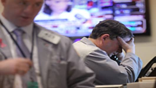 A trader holds his head in his hand on the floor of the New York Stock Exchange in New York City