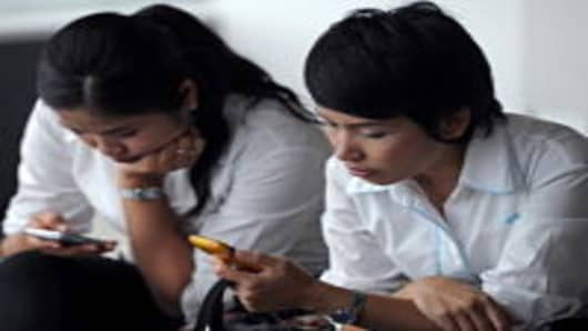 Women use mobile phones during a break at an office building in Bangkok.