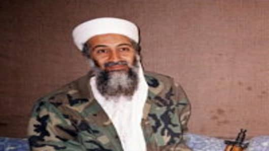 Saudi-dissident Osama Bin Laden sits on floor with his AK-47 rifle in his hide outs in Afghanistan 08 November, 2001. Osama bin Laden in an intervie
