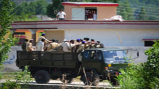 Pakistani army soldiers leave the area near the hideout of Al-Qaeda leader Osama bin Laden after a ground operation by US Special Forces in Abbottabad on May 2, 2011.
