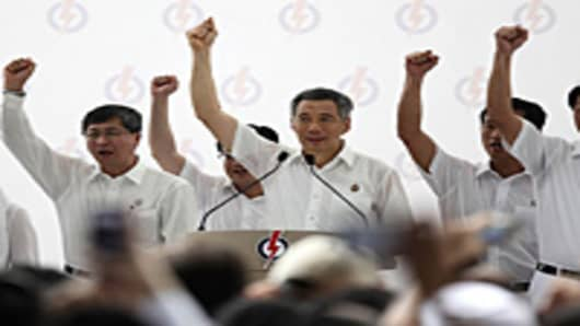 Prime Minster and the Secretary General of the People's Action Party, Lee Hsien Loong, leads a cheer together with the party members during a rally on May 3, 2011 in Singapore.