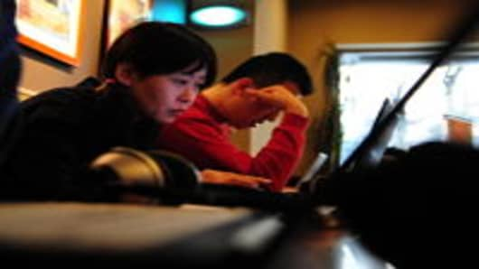 A woman surfs the internet on a laptop computer at a wireless cafe in Beijing, China.