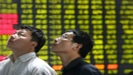 Investors watch a display at a stock exchange in Huaian, Jiangsu Province, China.
