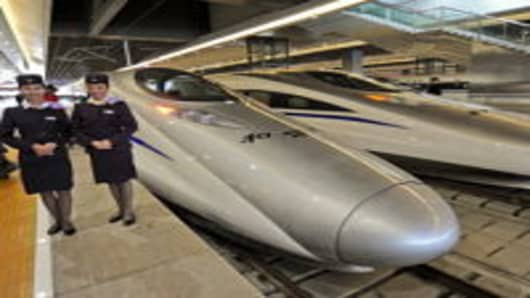 Rail attendants pose with the Chinese high-speed trains at a station in Shanghai on October 26, 2010, prior to the launch of the