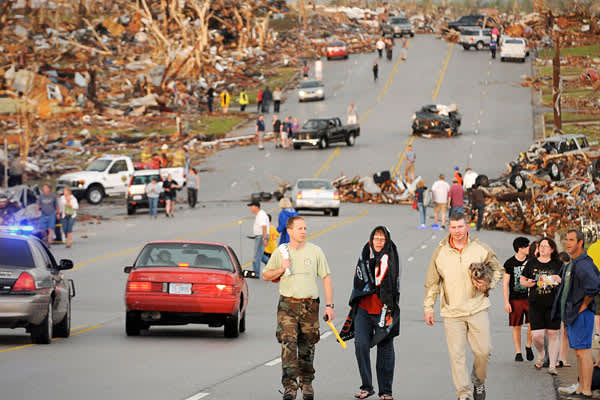 A massive tornado that tore a 6-mile (10-kilometer) path across southwestern Missouri killed at least 89 people as it slammed into the city of Joplin. Here, residents of Joplin walk down the street after the May 22 tornado.