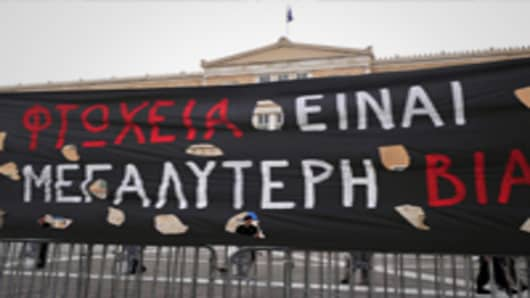 Greek riot police officers stand guard in front of the Greek parliament next to a banner reading ' Poverty is the biggest brutality ' during a general strike against government austerity plans, in Athens.