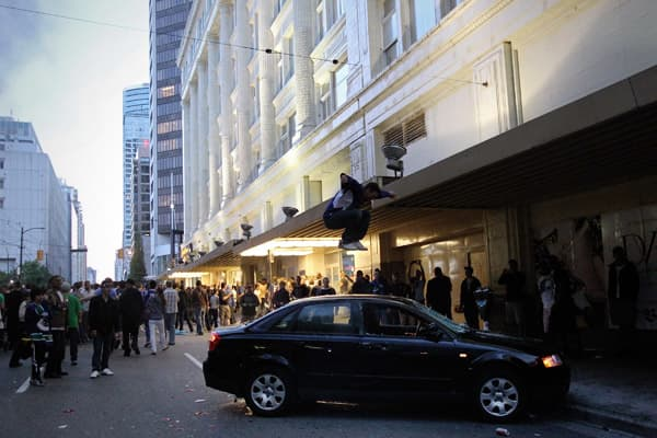 A rioter jumps on the top of a car on June 15, 2011 in Vancouver, Canada.