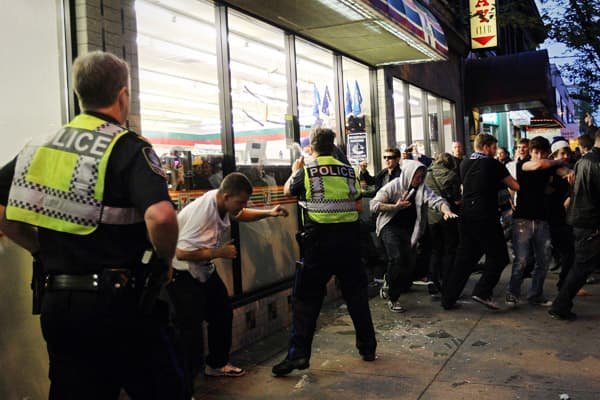 Police officers pepper spray a group of rioters trying to break into a 7-11.