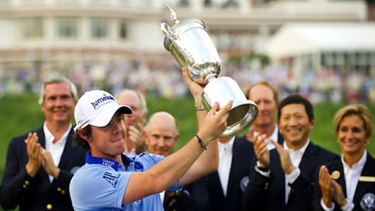 ory McIlroy of Northern Ireland holds up the trophy after winning the 111th US Open by eight strokes over Jason Day with a record 268 at Congressional Country Club on June 19, 2011, in Bethesda, Maryland.