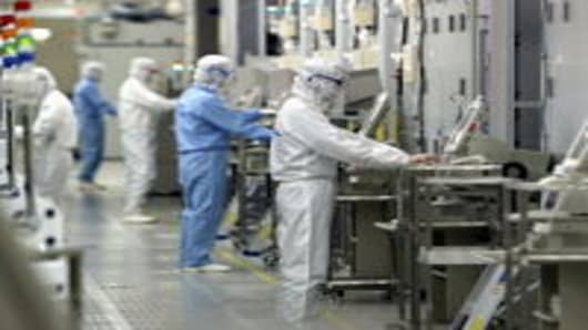 Technicians at work in the clean room of the Fab Equipment at a semiconductor company, Renesas Technology Corp. on June 17, 2004 in Ibaraki, Japan. Renesas is the first company to produce semiconductor products from 300mm wafer in the world.