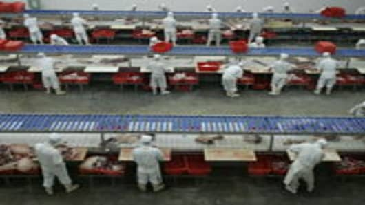 Workers process pork at a slaughtering factory September 26, 2007 in Beijing, China.