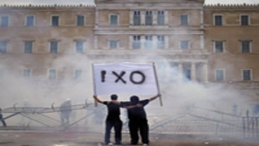 Amid tear gas, demonstrators hold a banner reading 'NO' during clashes with riot police in front of the Greek Parliament.