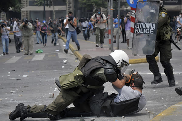 A riot policeman arrest a protester during clashes in front of the Greek Parliament on June 29, 2011 in Athens as lawmakers moved towards a vote on a massive austerity package demanded by international creditors.