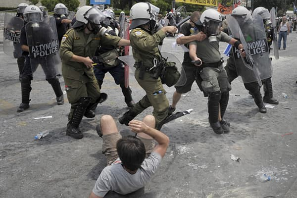Demonstrators clash with riot police in front of the Greek Parliament on June 29, 2011 in Athens as lawmakers moved towards a vote on a massive austerity package demanded by international creditors.