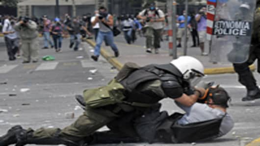 A riotpoliceman arrest a protestor during clashes in front of the Greek Parliament.