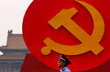 A policeman patrols under a giant communist emblem on the Tiananmen Square on June 28, 2011 in Beijing, China.