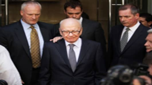 News Corp. Chairman Rupert Murdoch looks down as he leaves the One Aldwych Hotel surrounded by his personal security team to speak with reporters after meeting with the family of murdered school girl Milly Dowler on July 15, 2011 in London, England.