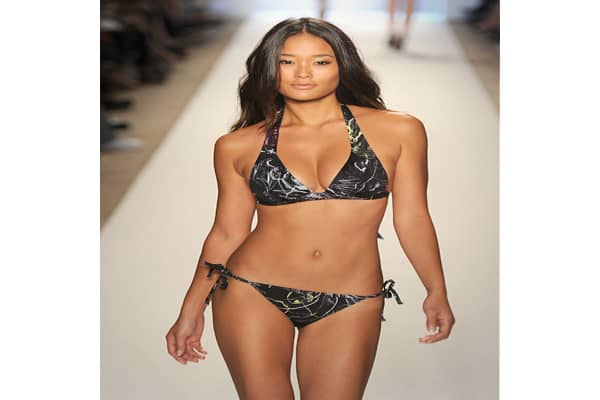 "A model wears a swim suit during Mercedes-Benz Fashion Week Swim in Miami Beach, Fla. The designer said its theme was a ""tropical utopia,"" but the suits in the collection had a variety of motifs."