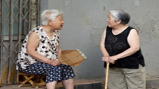Two old women chat outside their homes in Hutong XiSi, one of the old neighborhoods in Beijing, China.