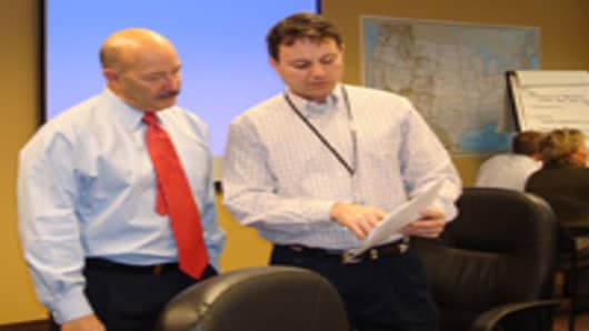 Ken Melchiorre, right, CH2M Hill's vice president for government facilities and infrastructure, leads a disaster response training session at the company's office in Washington, D.C.