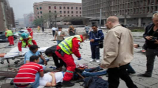 njured people are treated by medics at the scene of an explosion near the government buildings in Norway's capital Oslo.