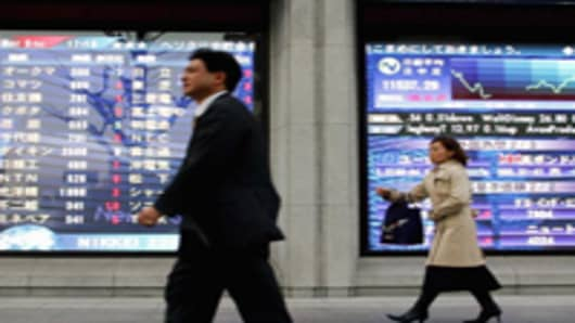 Investors pass by an electric board showing the figure of Nikkei stock average in Tokyo, Japan.