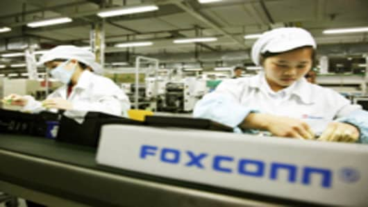 Employees work on the assembly line at Hon Hai Group's Foxconn plant in Shenzhen, Guangdong province, China.