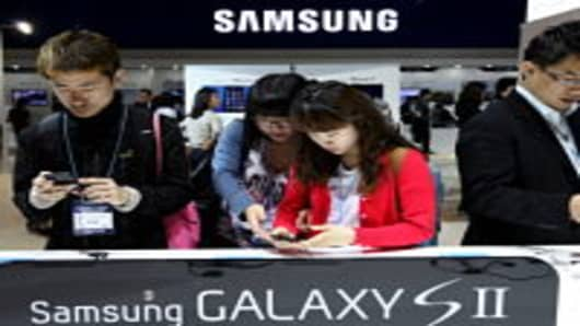 Visitors inspect Samsung Electronics Co.'s Galaxy S II smartphones at the World IT Show 2011 in Seoul, South Korea, on Wednesday, May 11, 2011.