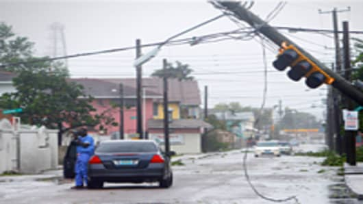 Man takes pictures of utility poles downed from winds from Hurricane Irene, New Providence Island, Bahamas.