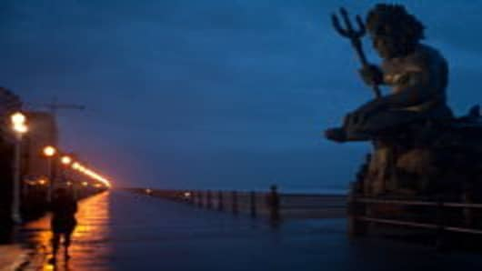 Susan Petrella, lower left, stands near the King Neptune statue as the first wind and rain of Hurricane Irene blow in on August 27, 2011 in Virginia Beach, VA.