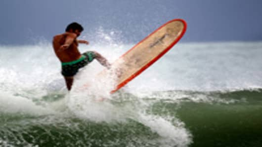 CJ Macias rides his surf board as he takes advantage of the waves created by Hurricane Irene as it passes off the coast on August 25, 2011 in Fort Lauderdale, Florida.