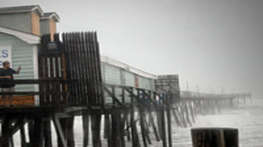 Denis Hromin stands on a pier to get a picture of the beach during Hurricane Irene August 27, 2011 in Kill Devil Hills, North Carolina. Hurricane Irene hit Dare County, which sits along the Outer Banks and includes the vacation towns of Nags Head, Kitty Hawk and Kill Devil Hills.