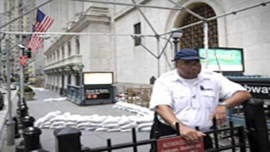 A security guard near the sand bagged front entrance of the New York Stock Exchange August 27, 2011. New York City ordered more than 300,000 people who live in flood-prone areas to evacuate as Hurricane Irene is forecast to reach the city.