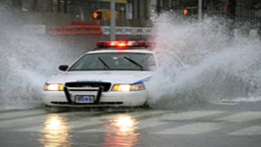 A New York City Police car drives through a flooded intersection on 43nd Street in New York on August 28, 2011 as Hurricane Irene hits the city and Tri State area with rain and high winds.