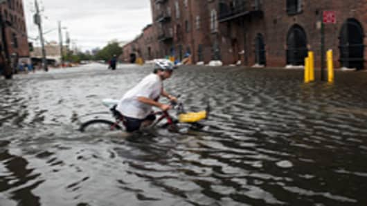 A local resident of Red Hook, Franklin Mount, crosses a flooded street on his bicycle in Red Hook, Brooklyn.