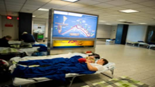 A young couple from Germany rest on a cot at LaGuardia Airport August 29, 2011 in New York.