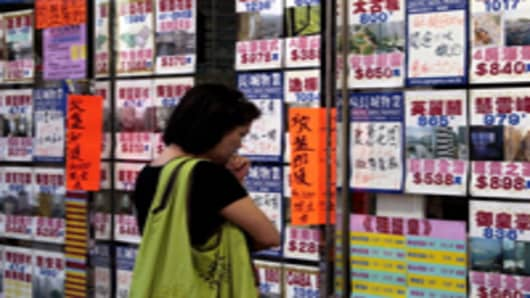 A woman looks at advertisments in the window of an estate agency in Hong Kong, China.