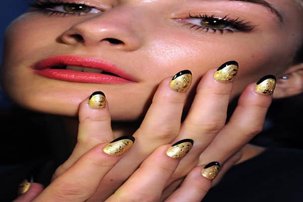 "CND's Manacchio also worked on Norman Ambrose's spring 2012 show during New York Fashion Week. Six different nail looks were used to portray a theme of a glamorous woman ""who swims in her diamonds."" Pictured here are nails painted in gold, edged in black and treated with gold leafing. Models wore other hues and textures ranging from gold to red to nudes. All nail looks incorporated the slender, almond-shaped nail trend."