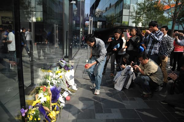 People mourn Apple co-founder Steve Jobs at an Apple store at Sanlitun Village on October 06, 2011 in Beijing, China.