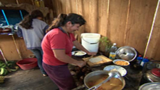 Guzman's wife and her assistant are busy in the camp kitchen, preparing dinner for the CNBC crew.