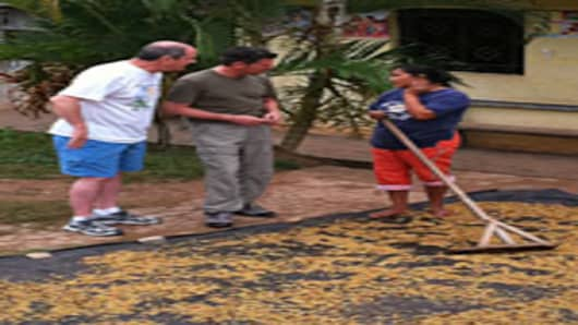 CNBC's Scott Wapner talks with a Peruvian woman drying coffee beans in her f