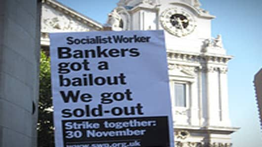 "A London demonstrator vents anger at bankers while standing near St. Paul's Cathedral. ""Occupy"" protestors, as they're known in the United States and United Kingdom, concern themselves primarily with what they see as the domination of society by interests within financial institutions and corporations."