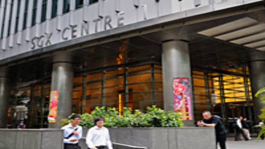 Pedestrians walk past the headquarters of the Singapore Exchange located in the SGX Centre in Singapore.