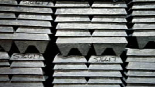 Zinc ingots, used to coat galvanized nails, sit stacked in a warehouse.