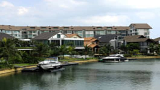 Private yachts are berthed outside luxury homes and condominium apartments at Sentosa Cove in Singapore.